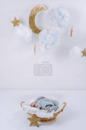 adorable newborn baby sleeping in basket with decorative clouds, moon and stars above head