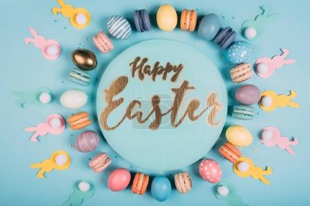 Photo for Top view of round board with happy easter lettering and colorful easter decor around on blue surface - Royalty Free Image