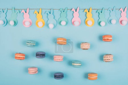 Photo for Top view of easter rabbits garland and colorful macarons on blue surface - Royalty Free Image