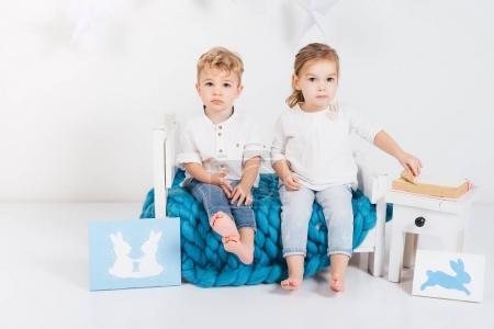 Photo pour Mignons petits enfants assis sur plaid tricoté bleu avec des livres et des cartes de lapin, concept de Pâques - image libre de droit