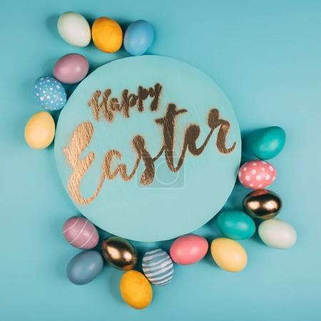 Photo for Top view of round board with happy easter lettering and various colorful easter eggs on blue surface - Royalty Free Image
