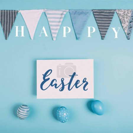 top view of greeting card with happy easter lettering and easter eggs on blue surface