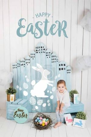 adorable little child sitting in easter decorated room with happy easter lettering