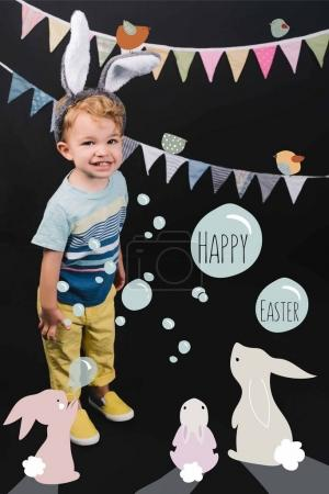 adorable little kid with bunny ears and garland smiling at camera on black, happy easter lettering in bubbles and bunnies collage