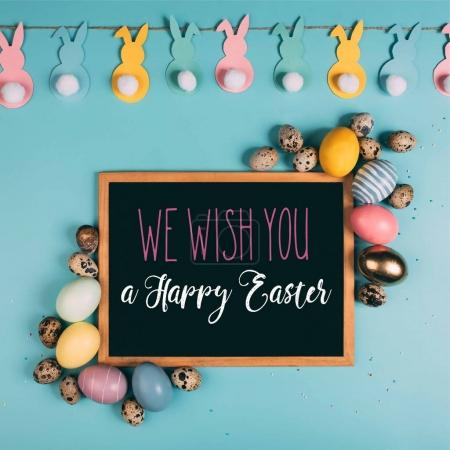 top view of colorful easter eggs and we wish you happy easter lettering chalkboard on blue surface
