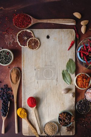 Photo for Various indian spices in wooden spoons, seeds, herbs and nuts and empty wooden board on dark stone table. Colorful spices, top view, selective focus, space for text. Organic food, healthy lifestyle - Royalty Free Image