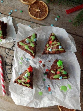 Photo pour Idées de nourriture de Noël, délicieux brownies au chocolat en forme de sapin de Noël sur fond de bois rustique. Concept de décoration confortable, vue de dessus, mise au point sélective . - image libre de droit