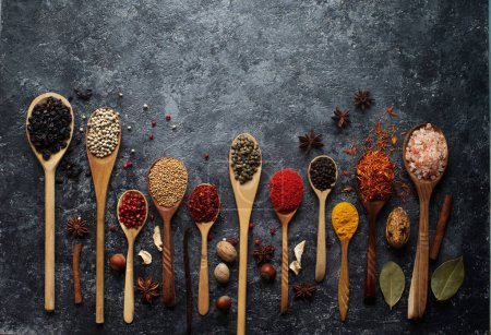 Various indian spices in wooden spoons, herbs and nuts
