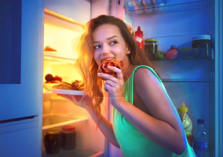 Photo for Beautiful teenage girl taking food from refrigerator at night - Royalty Free Image