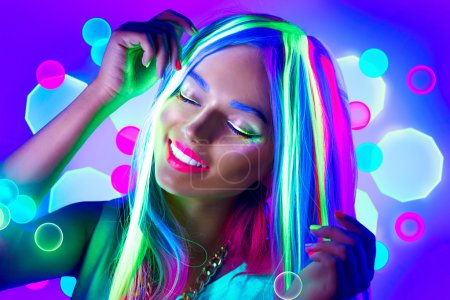 Young woman dancing in neon light