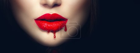 Photo for Sexy vampire red lips with dripping blood closeup isolated on black background - Royalty Free Image