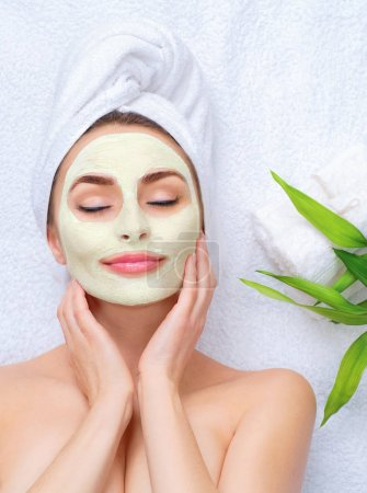 Spa girl with towel on head applying facial clay mask