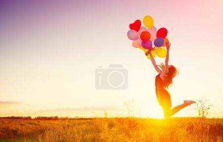 girl running and jumping on summer field with colorful air balloons over sunset sky