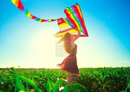 redhead girl with flying colorful kite over clear blue sky