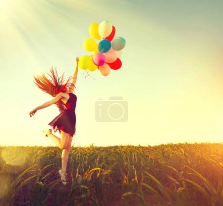 redhead girl running and jumping on summer field with colorful air balloons over clear blue sky