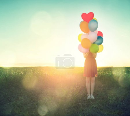 teenage girl on summer field with colorful air balloons over clear sky