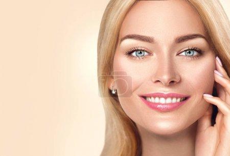 Photo pour Femme blonde souriante sur fond beige - image libre de droit