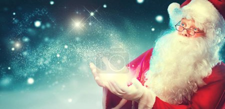 Photo for Happy Santa Claus with magic lights on blue background - Royalty Free Image