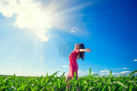 girl on summer field rising hands over blue sky