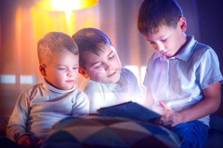 Three little boys with tablet computer in dark room