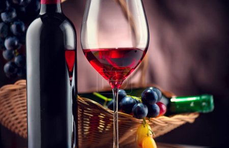 Bottle and glass of red wine with ripe grapes over black background