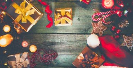 Foto de Regalos de Navidad, velas, bastones de caramelo y pan de jengibre en la mesa de madera verde - Imagen libre de derechos