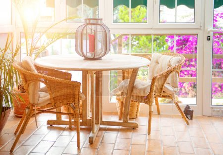 Interior of empty cafe terrace with table and wicker chairs