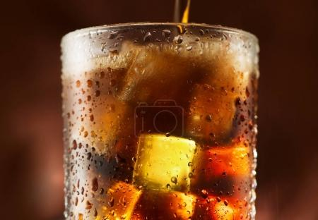 Photo pour Cola verser dans du verre avec des glaçons sur fond sombre - image libre de droit