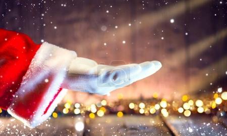 Foto de Santa Claus mostrando la palma abierta de la mano sobre fondo de madera con guirnaldas - Imagen libre de derechos