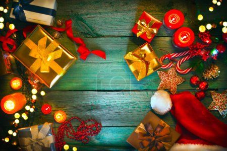 Christmas gifts, candles, candy canes and gingerbread on green wooden table