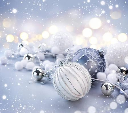 Silver Christmas decorations on blurred grey background with lights