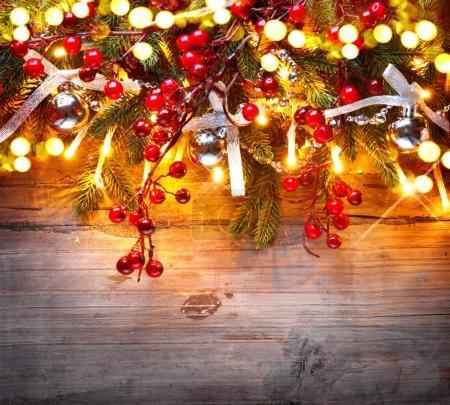 Christmas tree decorated with lights and berries over wooden background