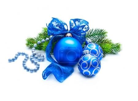 Blue Christmas decoration balls with fir branch and ribbon on white background