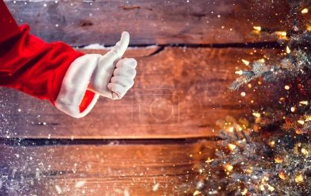Santa Claus thumb up gesture over wooden background