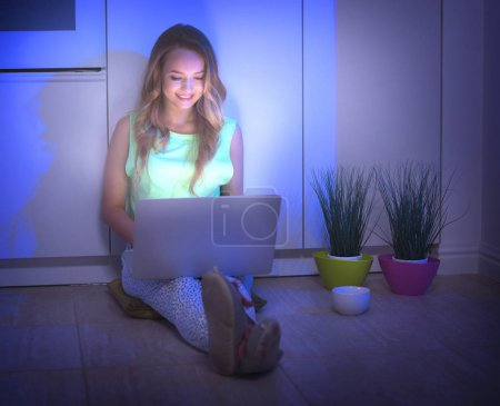 girl sitting on floor at night and using laptop computer
