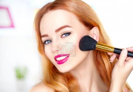 Young girl applying makeup with big brush