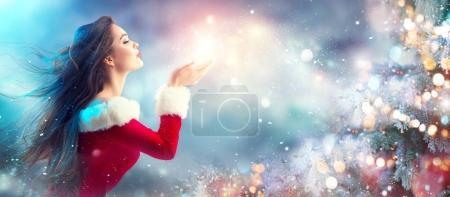 Photo pour Brunette jeune femme en costume de Père Noël soufflant de la neige sur fond flou de vacances - image libre de droit