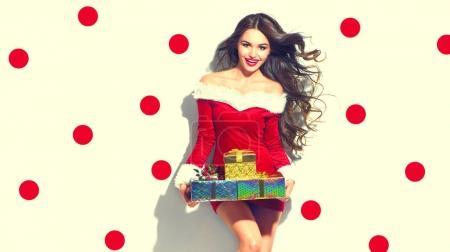 Foto de Modelo chica usando Santa Claus traje y la celebración de regalos en fondo de puntos - Imagen libre de derechos