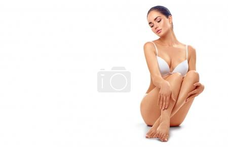 Young woman in white underwear touching legs