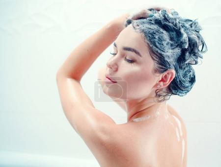 Young woman taking shower and washing long black hair