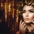 Woman with fashion golden makeup and accessories...