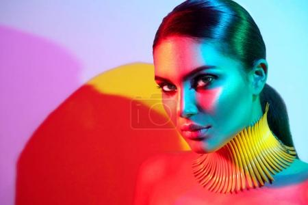 Fashion model in colorful bright lights with trendy make-up