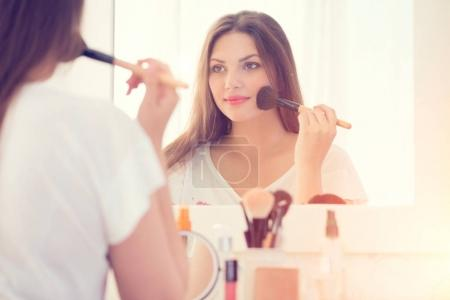 Young girl looking in mirror and applying makeup