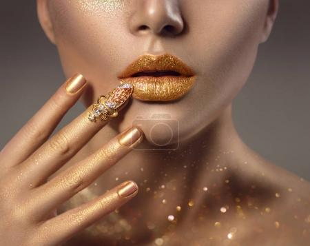 Woman with golden makeup and golden nail accessory on finger