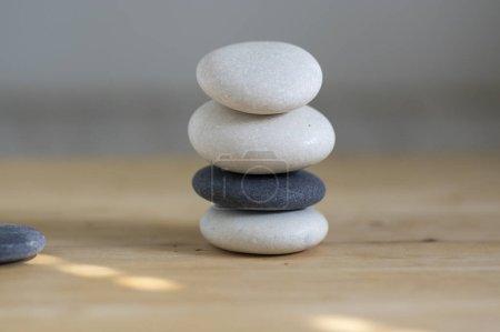 Photo pour Cairn en pierre sur fond bois, tour en pierres, pierres simples, harmonie et équilibre, sculpture rock zen, galets noirs et blancs - image libre de droit