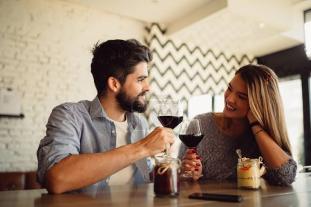 Couple clink glasses with red wine at date in casual outfit in cafe. Couple having romantic moments.