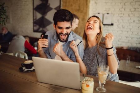 Happy young couple shopping online.