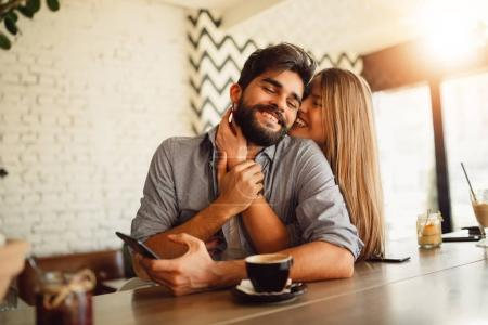 Portrait of a beautiful couple while having romantic moments in cafe. Girl hugging her handsome boyfriend.