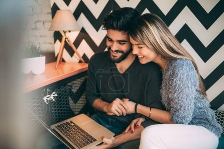 Happy couple watching something on laptop at cafe, surfing on internet or video chatting.