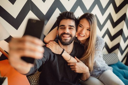 Beautiful loving couple enjoying in a coffee shop while making selfie.